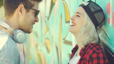 Two-hipster-friends-chatting-in-front-of-graffiti