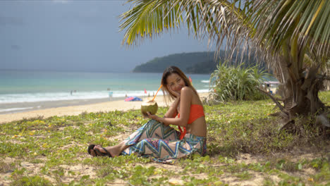 Happy-woman-with-coconut-drink-resting-on-beach