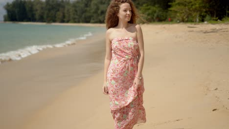 Pleasant-woman-holding-flowered-dress-and-walking-on-sandy-beach-in-bright-day