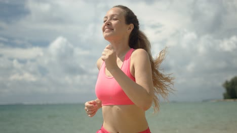 Pleasant-woman-in-pink-sweatsuit-running-on-beach