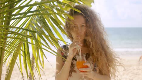 Attractive-female-drinking-beverage-beside-palm-tree