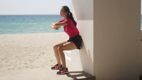 Young-woman-doing-wall-squats-on-beach