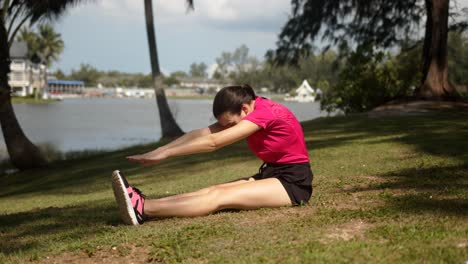 Sporty-woman-doing-stretching-exercise-on-lakeside