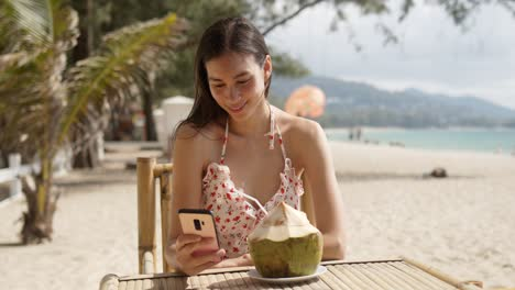 Smiling-woman-drinking-coconut-water-and-using-smartphone-on-beach
