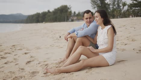 Young-lovers-tourists-sitting-on-beach