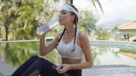 Sporty-female-drinking-water-during-workout