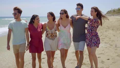 Happy-group-of-young-students-walking-on-a-beach