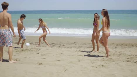 Group-of-Friends-Kicking-Ball-on-Sunny-Beach