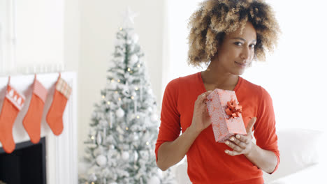 Smiling-woman-holding-a-Christmas-gift