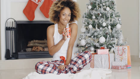 Smiling-young-woman-enjoying-a-cup-of-Xmas-coffee