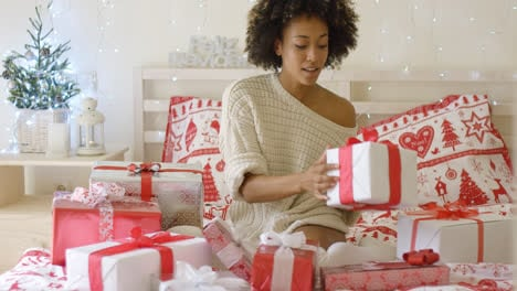 Young-woman-sitting-in-bed-surrounded-by-gifts