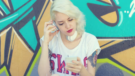 Trendy-young-woman-with-tattoos-listening-to-music