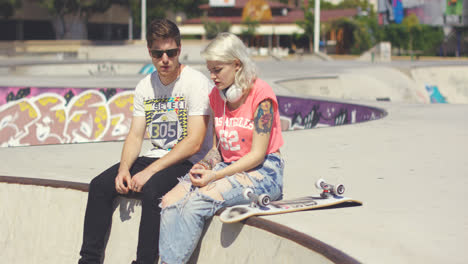 Young-couple-of-skateboarders-sitting-chatting