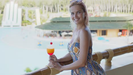 Cheerful-lady-with-fruit-drink-on-balcony-near-swimming-pool