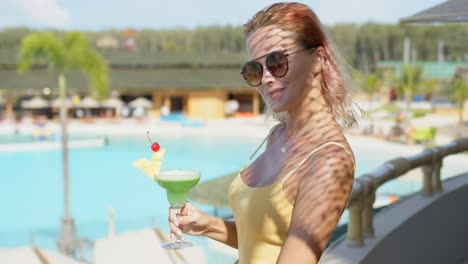 Stylish-woman-with-green-beverage-on-hotel-terrace
