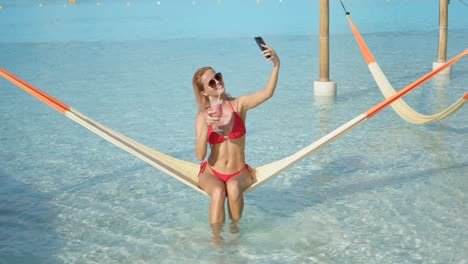 Cheerful-woman-with-cocktail-taking-selfie-on-hammock