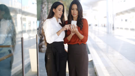 Two-businesswomen-checking-a-phone-message