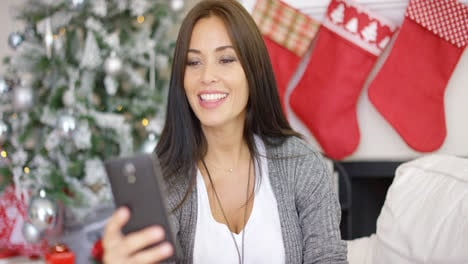 Happy-young-woman-taking-a-selfie-at-Christmas