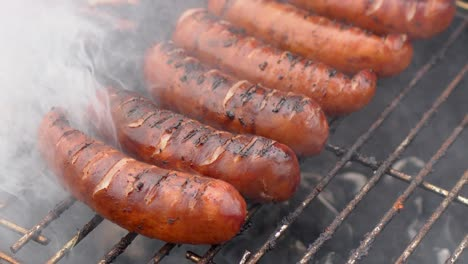 Hot-tasty-grilled-sausages-frying-on-smoking-barbecue-Slow-motion-video