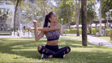 Sporty-woman-sitting-with-crossed-legs-and-stretching-arms-in-park