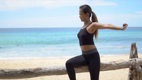 Fit-lady-stretching-arms-on-beach