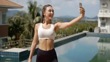 Cheerful-sportswoman-taking-selfie-on-poolside