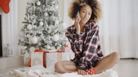 Young-woman-relaxing-in-front-of-a-Christmas-tree