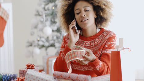 Young-woman-chatting-on-her-mobile-at-Christmas