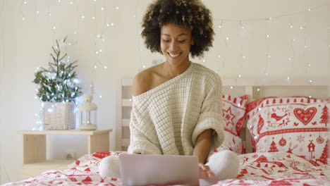 Happy-woman-in-sweater-on-bed-using-computer