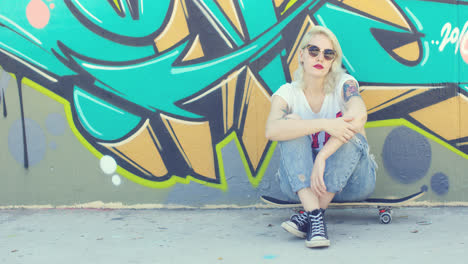 Young-woman-sitting-waiting-on-her-skateboard