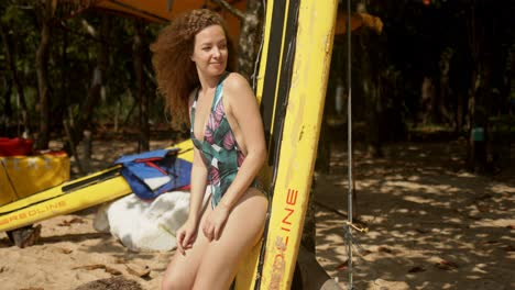 Young-woman-standing-next-to-paddle-board-on-beach