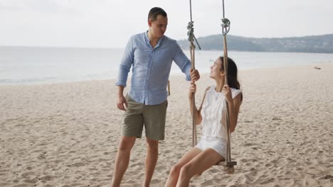 Man-teetering-woman-on-swing-at-lonely-coastline