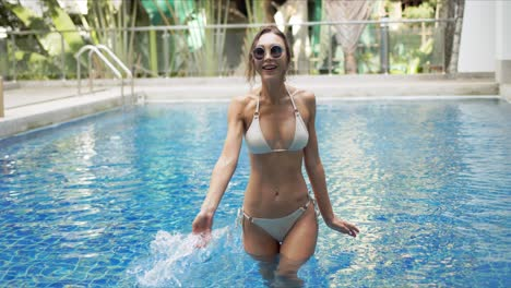 Cheerful-female-splashing-water-in-swimming-pool