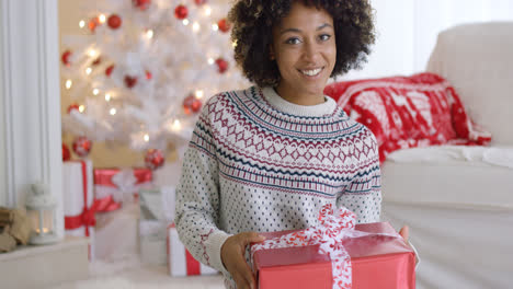 Excited-young-woman-holding-up-a-Christmas-gift