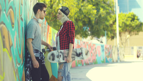 Trendy-young-couple-chatting-in-an-urban-street