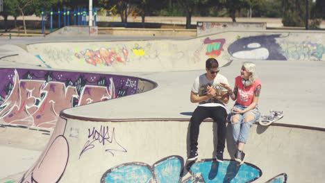 Young-couple-sitting-on-a-wall-at-a-skate-park