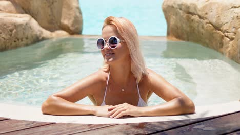 Content-woman-in-sunglasses-lounging-in-cool-pool-with-crystal-water