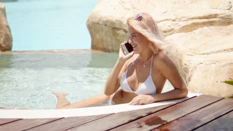 Pleasant-woman-cheerfully-speaking-on-smartphone-while-swimming-in-pool