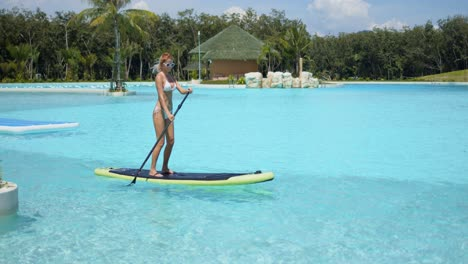 Woman-floating-on-paddle-board-in-large-swimming-pool
