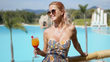 Delighted-woman-with-cocktail-on-hotel-terrace