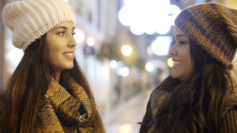 Two-young-woman-chatting-outdoors-in-winter
