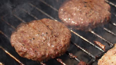 Tasty-two-hamburger-meat-frying-on-smoking-hot-barbecue-Slow-motion-video