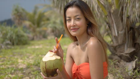 Positive-woman-drinking-coconut-cocktail