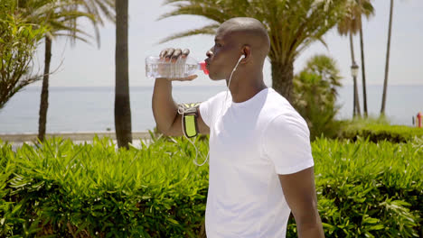 Side-view-of-black-athletic-man-drinking-water