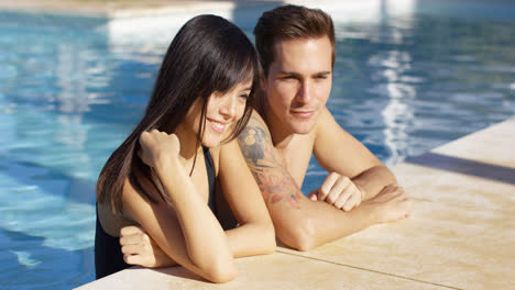 Diverse-good-looking-couple-stand-in-swimming-pool
