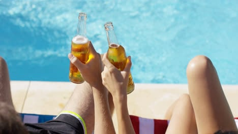 Couple-relaxing-at-the-pool-with-beers