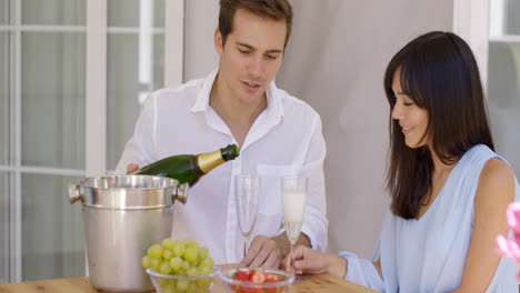Smiling-young-couple-pouring-champagne-to-drink
