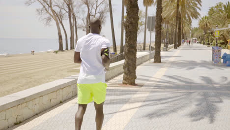 Muscular-young-man-out-jogging-on-a-promenade