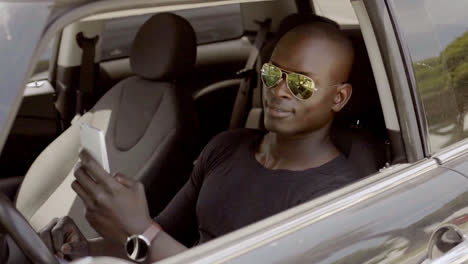 Handsome-black-man-seated-in-car-with-phone