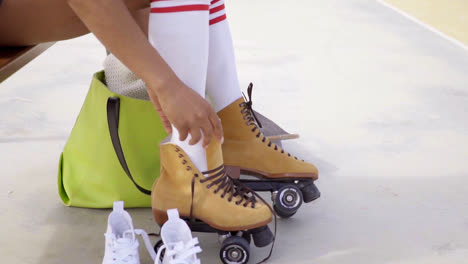 Young-woman-sits-on-bench-to-tie-her-skates
